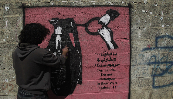 Artist Murad Subai paints a graffiti depicting a grenade on a street in Sanaa