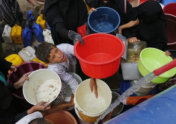 2015-07-04 13:49:25 epa04831554 Yemenis fill buckets with water from a donated source amid disruption of water supplies, in Sana'a, Yemen, 04 July 2015. Many Yemenis are suffering from a lack of basic services and resources, in a humanitarian disaster dramatically worsened by a blockade imposed by the Saudi-led coalition targeting the Houthi rebels' and allied positions in the impoverished Arab state.  EPA/YAHYA ARHAB