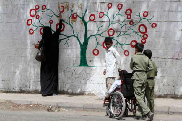 An activist paints graffiti on a wall in Sanaa June 7, 2012. Since last month, a group of young artists took to the streets of Sanaa using graffiti as a medium to promote peace in neighbourhoods. REUTERS/Mohamed al-Sayaghi (YEMEN - Tags: CIVIL UNREST SOCIETY)