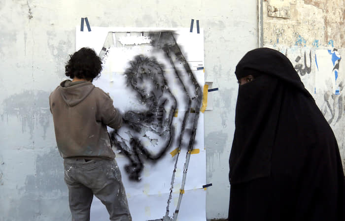 epa05595530 A picture made available on 21 October 2016 shows a Yemeni artist spraying a graffiti on a wall in protest against the ongoing conflict and the worsening economic situation in the war-affected country, in Sana'a, Yemen, 20 October 2016. According to reports, since March 2015, ongoing conflict and the Saudi-led airstrike campaign in Yemen have left 21.2 million - 82 percent of Yemen's population - in dire need of humanitarian aid, including 9.9 million children.  EPA/YAHYA ARHAB