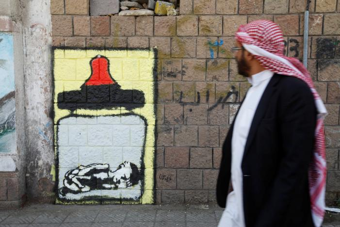 A man walks pass a graffiti by artist Thi Yazen AL-Alawy depicting a bottle of milk with a malnourished child inside along a street in Sanaa, Yemen, October 20, 2016. REUTERS/Mohamed al-Sayaghi
