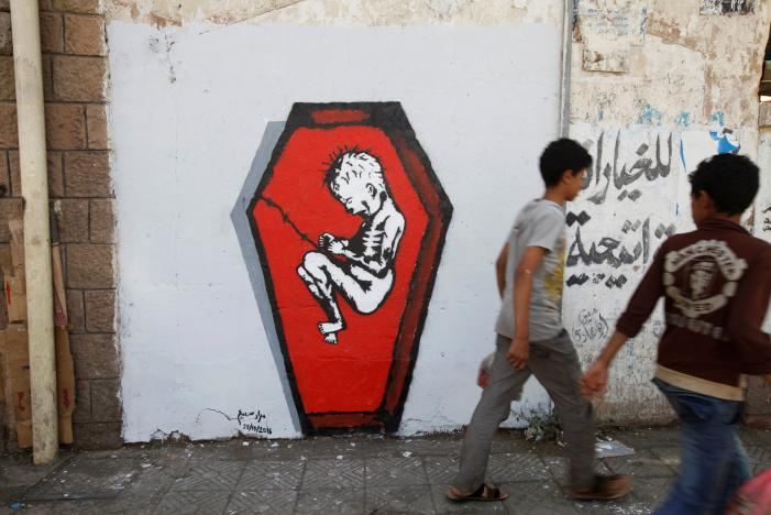 Boys walks pass a graffiti of artist Murad Subai depicting a child suffering from malnutrition in a coffin along a street in Sanaa, Yemen, October 20, 2016. REUTERS/Mohamed al-Sayaghi